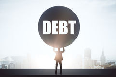 Debt concept. Struggling businessman holding huge ball on bright city background. Debt concept Stock Photo