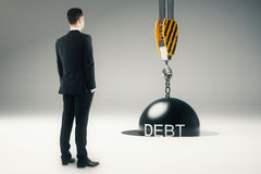 Debt concept wrecking ball. Debt concept with businessman looking at crane hook with wrecking ball going into pit. 3D Rendering Stock Photo