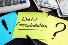 Debt consolidation written by hand and money. Debt consolidation written by hand and money on the table royalty free stock images