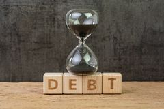 Debt, financial obligation driving economic bubble burst countdown concept, sandglass or hourglass on wooden cube block with. Alphabet building the word Debt on stock photography