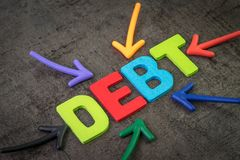 Debt, financial obligation that you borrow money and have to pay back concept, multi color arrows pointing to the word Debt at the. Center of black cement royalty free stock images