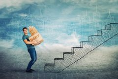 Debt. Frustrated young man too much burden, lean back carrying heavy boxes with debt word text, have to climb a staircase. Concept of difficult life road, a lot stock image