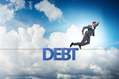 Debt and loan concept with businessman walking on tight rope. The debt and loan concept with businessman walking on tight rope royalty free stock image