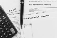 Debt, loans, bills, calculator. Debt, loan, bills, bank statements, direct debits agreements, calculator and a pen stock photos
