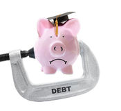Debt piggy bank vice. Frowning piggy bank wearing graduation cap being squeezed in a Debt vice Royalty Free Stock Image
