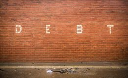 Debt On Red Brick Wall Stock Photos