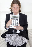 Debt Sucks. A businessman with money on his lap miserably points to an oversized calculator with a negative number Royalty Free Stock Photo