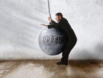 Debt win. Wrecking ball as the debt knock out the businessman Royalty Free Stock Photo