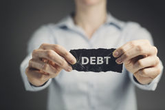 Debt. Woman holding a label with the word debt toward the camera royalty free stock photos