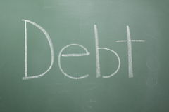 Debt written on chalkboard Royalty Free Stock Image