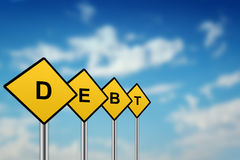 Debt on yellow road sign. With blurred sky background Stock Photos