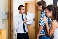 Debts collector and family couple standing in doorway. Debts collector and upset spanish family couple standing in doorway of flat stock image
