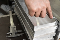 Deburring of steel plates after milling. In his hand a simple cu Royalty Free Stock Photography
