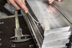 Deburring of steel plates after milling. In his hand a simple cu Royalty Free Stock Photos