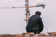 18 Dec,2014 Beijing. a men on a construction site in City with cranes ,takeing Bricks. And.building train station royalty free stock photography