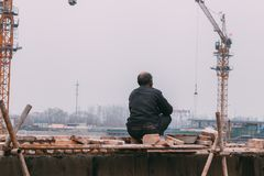 18 Dec,2014 Beijing. a men on a construction site in City with cranes ,takeing Bricks a==. 18 Dec,2014 Beijing. a men on a construction site in City with cranes stock image