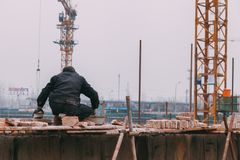 18 Dec,2014 Beijing. a men on a construction site in City with cranes ,takeing Bricks. And.building train station stock photography