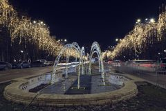 13 DEC 2018, Romania, Bucharest. Bulevardul Unirii Christmas lights, fountain and traffic in front of the Parliament. Long. Exposure. Selective focus royalty free stock photo