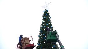 15 Dec 2017. Russia. The City Of Domodedovo. Central square. Workers hang a festive balls on a large urban Christmas stock video