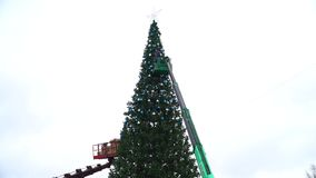 15 Dec 2017. Russia. The City Of Domodedovo. Central square. Workers hang a festive balls on a large urban Christmas stock video footage