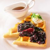 A decadent breakfast plate of Belgian waffles, whipped cream, and maple syrup. royalty free stock photos