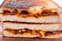 Decadent grilled cheese and bacon sandwiches with oozing cheese Stock Image