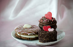 Decadent  pastries for valentines day. Three decadent pastries are on a plate for the sweetest one you love. a chocolate whoopee pie, with white filling and pink Royalty Free Stock Photos