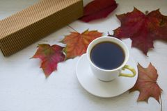 Decaf coffee on a small cup. On the maple leaves stock photography