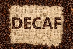 Decaf concept on brown coffee bag background. Decaf written with roasted beans as concept on brown coffee bag as background stock image