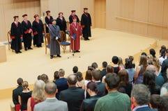 Decano dell'università e bordo dei funzionari che danno discorso alla graduation finale del diploma Fotografia Stock