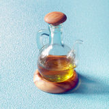 Decantatore di olio d'oliva vergine su un supporto di legno Fotografie Stock