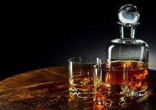 Decantatore di whiskey oltre a due vetri di metà riempita fotografia stock