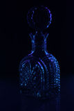 Decanter on a black background shining the blue Royalty Free Stock Images