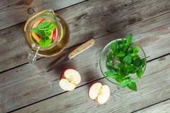 Decanter cool green tea with mint and cut apple Royalty Free Stock Photography