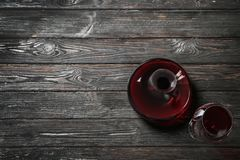 Decanter and glass with red wine. On wooden background, top view stock image