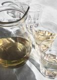 Decanter and glasses filled with homemade white Greek wine, on the table in a tavern in the sunlight and with beautiful shadows stock images