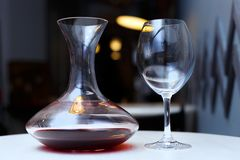 Decanter with red wine and glass on a table royalty free stock image