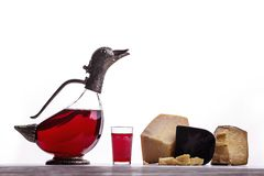A decanter of red wine, a glass of wine, expensive cheeses, cheese with mold, black cheese. On white background. Place for logo stock photos