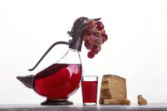 A decanter of red wine, a glass of wine, expensive cheeses, cheese with mold, black cheese and grapes. On white background. Place for logo stock photos