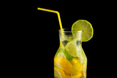 Decanter with soda water, lemons and a straw on a black background. Royalty Free Stock Images