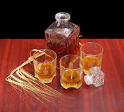 Decanter and three glasses with whiskey, several barley spikes Stock Photo