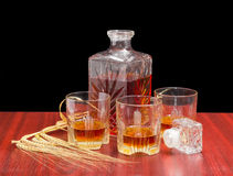 Decanter and three glasses with whiskey, several barley spikes Royalty Free Stock Photography