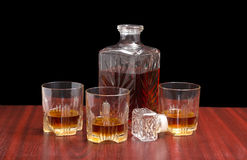 Decanter and three glasses with whiskey on a wooden table Royalty Free Stock Photo
