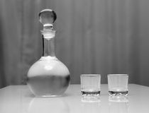 Decanter and two glasses with vodka standing on table Stock Photography