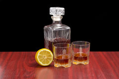 Decanter and two glasses with whiskey and lemon Stock Images