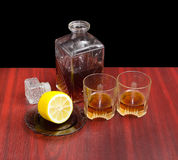 Decanter and two glasses with whiskey, lemon on a saucer Stock Photography