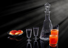 Decanter and two shot glasses with ice vodka, two salmon red caviar sandwiches on a glass plate and two glasses with. Multifruit juice on a black acrylic stock images