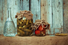 Decanter with vodka, pickles, marinated tomatoes and a shot glas Stock Images