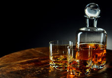 Decanter of whiskey besides two glasses half filled stock photography