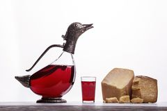 Decanter with wine in the form of ducks, glass with wine, Parma ham and expensive blue cheese. On white background stock photo